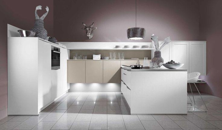 Witte design keuken met sfeerverlichting. Deze witte designkeuken zorgt door de gedurfde opstelling voor een speciale en unieke look. De keuken is voorzien van halfhoge, witte kolomkasten, zwevende kasten in een beige kleur en een kookeiland aan de muur. Door de sfeerverlichting komen de zwevende kasten nog net da tikkeltje meer op de voorgrond. Het kookeiland is voorzien van een inox werkblad met kookplaat en gootsteen.