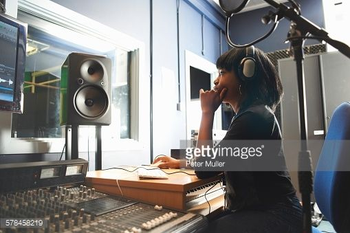 Stock Photo : Side view of young woman wearing headphones, sitting at mixing desk in recording studio looking at monitor