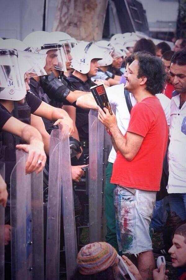 During Thursdays protests, a young man reads from a book to the police.  #occupygezi #direngeziparki #occupyturkey