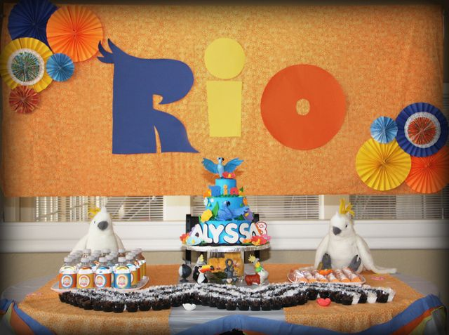 Rio party for Laura.  Great ideas.  Make the Rio sign from colored paper.  Layer Blue cake and put the characters on!  Love it.