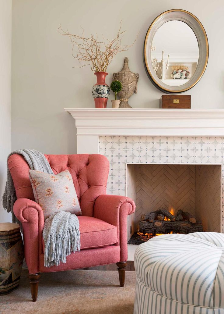 Cozy, Tufted Coral Chair With Floral Throw Pillow Next To Traditional Fireplace With Neutral Mantel and Tile Surround
