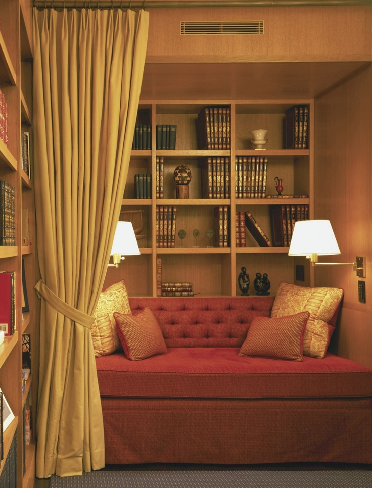 plush red daybed behind gold curtain with bookshelves