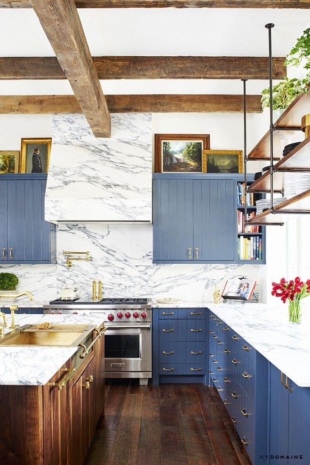 Brooklyn Decker's rustic inspired kitchen with exposed wooden beams, light blue cabinents, and marble