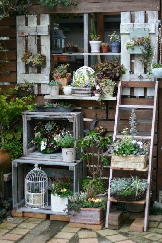 Hoog laag verschillen creëren met kistjes en trapje. Erg leuk zo met de bloempotten.