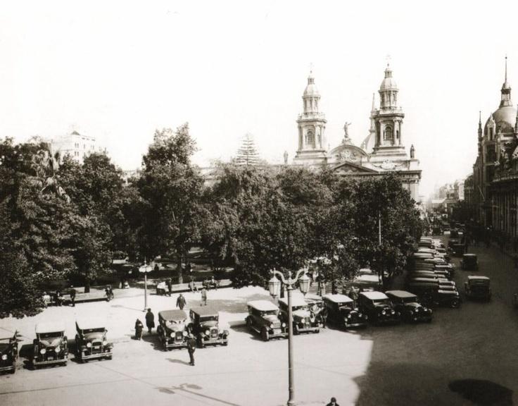 Plaza de Armas en 1930, rodeada de crecidos arboles, al fondo la Catedral y la cúpula del edificio de Correos de Chile que se quemo en un incendio.