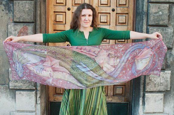 A large hand-painted silk scarf in purple and green, with a fairy-tale dragon and old town.