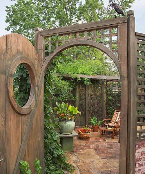 secret garden on urban plot beer garden with hops vine, arched doorway and lattice and brick wall
