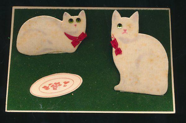 old postcard: Stoff-Präge-AK Weiße Katzen mit roten Schleifen sitzen vor weißem Teller