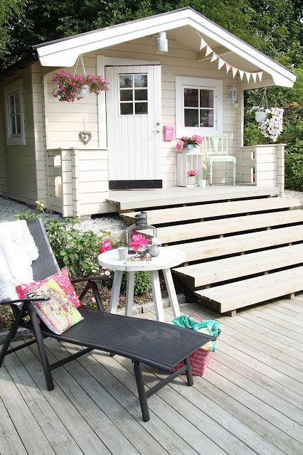 Georgeous summer house, I want one. Lovely white steps up to a striking summerhouse - love the bunting and sun lounger too.