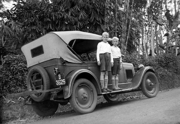 Twee Europese jongens op de treeplank van een auto bij Wates.  12-05-1931