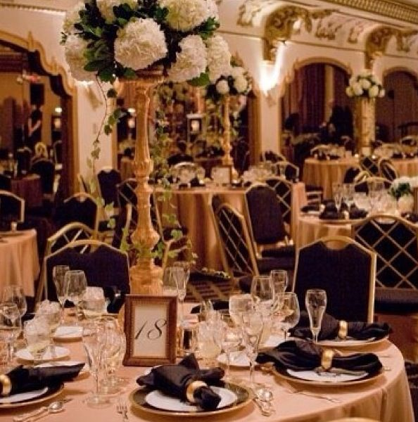 Tall centrepieces with white flowers and gold details. Gorgeous black tie event decor.