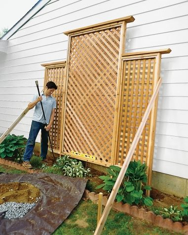 Lay the trellis on its face and tilt into the adjacent holes in the ground. Hold the trellis in place with 2x4s screwed to the sides as stabilizers and fill holes with soil mixed with some gravel, tamping it down every 6 inches.