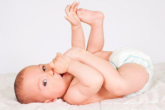 Baby mit fünf Monaten spielt mit seinen Füßen