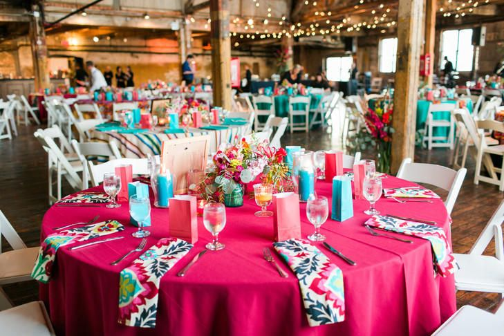 Colorful wedding reception table covered in a bright pink tablecloth