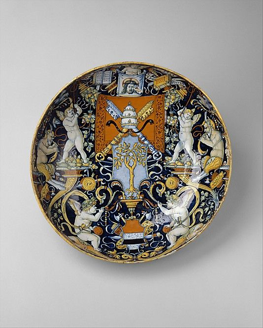 An Italian maiolica bowl, 1508, with the heraldic arms of Pope Julius II and the Manzoli of Bologna surrounded by putti, cornucopiae, satyrs, dolphins, birds, etc. (The Metropolitan Museum of Art)