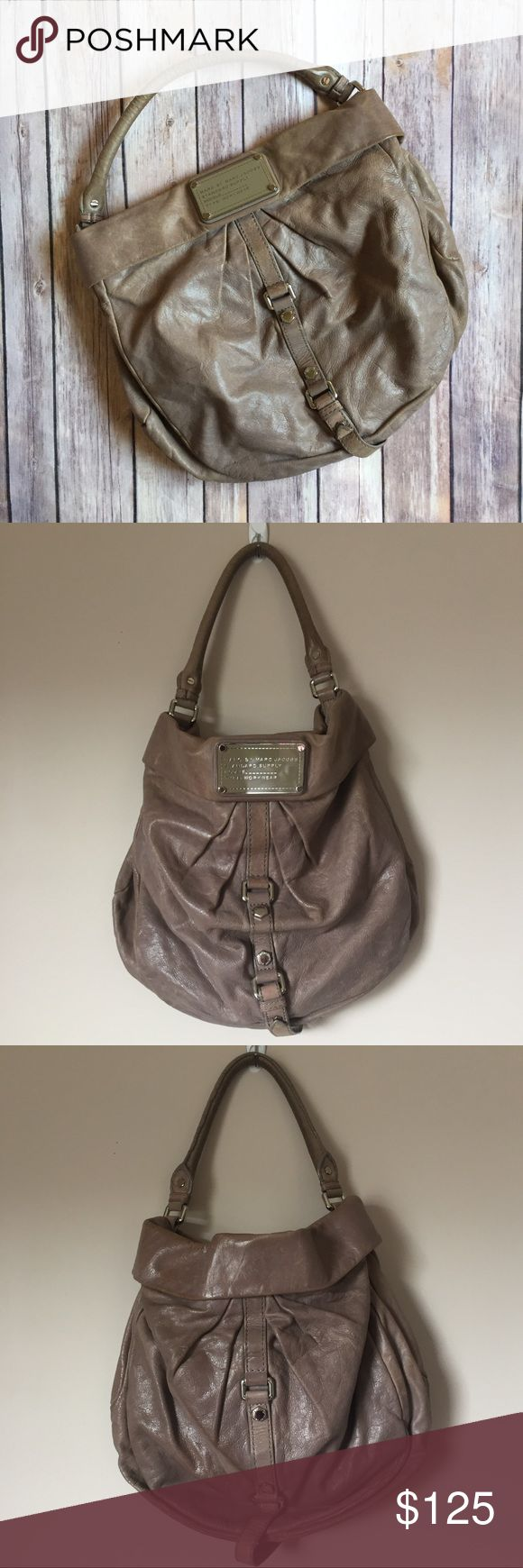 """MARC BY MARC JACOBS Standard Supply Workwear Sac MARC BY MARC JACOBS Standard Workwear Sac. Color: Taupe, genuine leather. Silver hardware and belted detail on front/back of bag. Magnetic closure. Green & black lining. Leather key holder. Large interior zipper pocket, 2 slip pockets. Approx 14""""L x 14""""H x 6""""D and 6"""" strap drop. Purchased at Bloomingdales. GUC, used a handful of times and has minor leather wear but not really noticeable because of the beautiful supple nature of the leather…"""