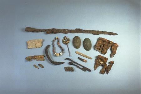 These objects were found in a woman's grave at Westness on Rousay in Orkney. She died in childbirth and was buried with her valuable jewellery and a range of tools between 850 and 900. The grave goods show that she was a woman of wealth and status. Some of the objects, such as the oval brooches and necklace, were brought over from Scandinavia. Others, such as the brooch pin, brooch made from a Gospel book plate and strap ends derive from the British Isles, obtained by looting or trade.