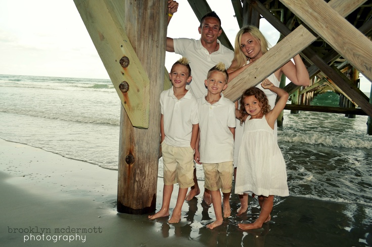 Family beach picture under pier a climb hang like a tree