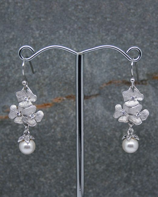Floral earrings with Swarovski pearl drops.  These very eye catching triple flower earrings should be a must for any occasion, perfect for weddings, anniversaries and birthdays.  The flowers measure 15 x 13mm approx and are each set with three crystals. The overall length of the earrings is 38mm from the top of the fitting.  Materials: Flowers: Rhodium plated over brass. Fittings: Hook fittings are silver plated. 6mm Swarovski pearls with rhodium plated over brass settings.  All of our...