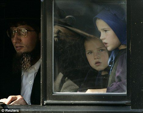 Shock: Amish sisters ride in their family buggy in a funeral procession for a young Amish girl who was a victim in the school shooting in October 2006