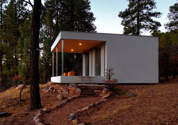 architect stephen atkinson designed this minimalist cabin for a client living in durango, colorado. the white house  features a kitchen and bathroom and open concept living area that holds the home's wood stove. the front of the  house has a covered patio which is the same size as the home's interior.