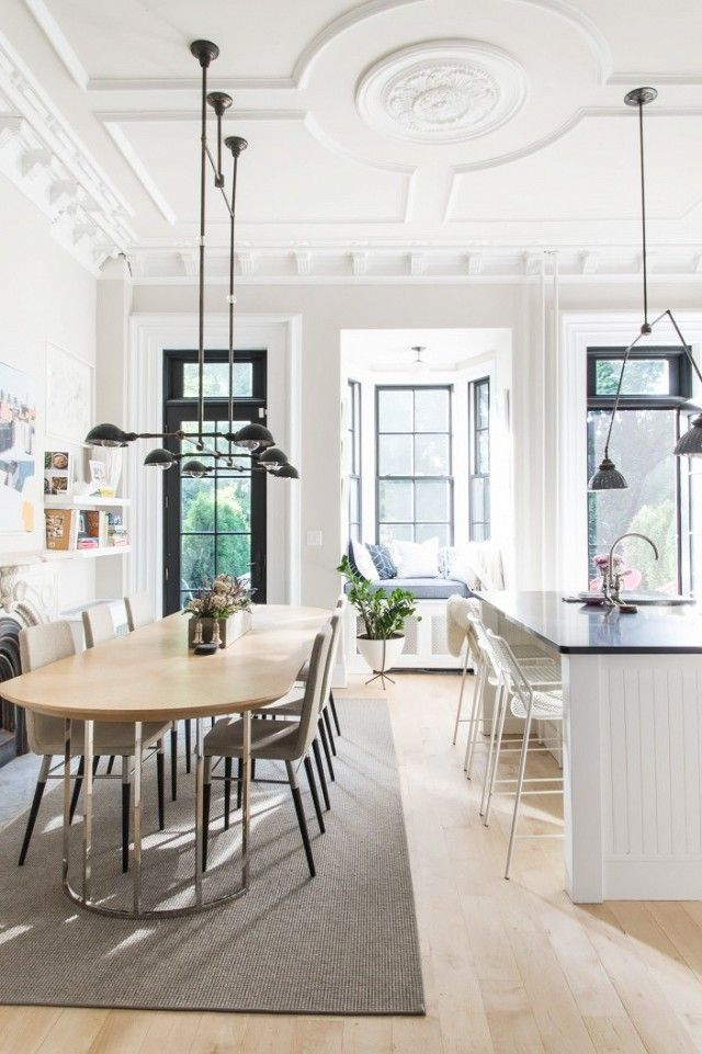 Open floor plan dining space with a long table, a black chandelier, and detailed ceilings