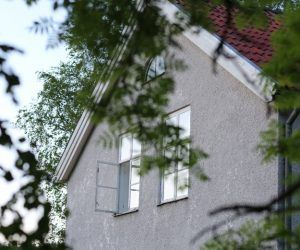 Claras hus med öppet sovrumsfönster på övervåningen i ljus sommarnatt.