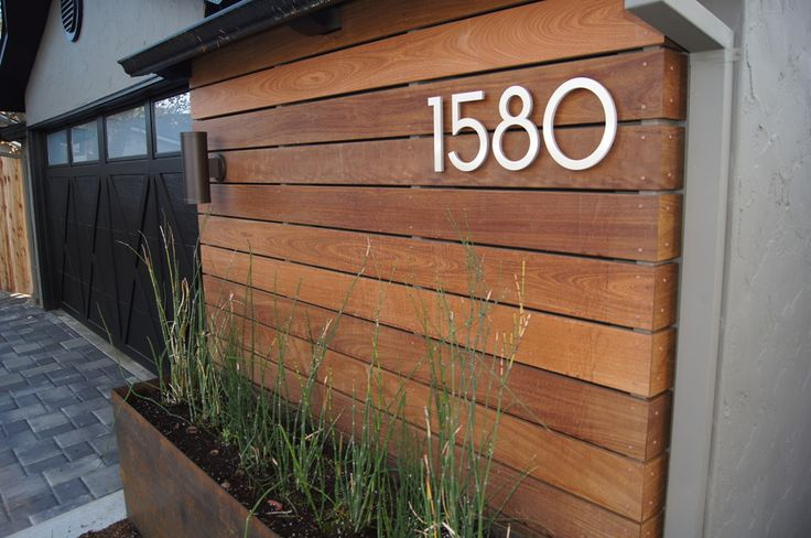 "Three of my favorite details of the new design are captured here: the new house numbers (which are 8"" tall and lit with a spotlight at night), the Ipê wood siding, and the custom raw steel planters."