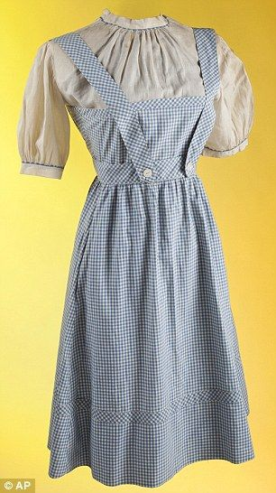 Icons and idols: Judy Garland, who plays Dorothy Gale in The Wizard of Oz (left) wore one of the most iconic on screen costumes in the 1939 film; her original dress (right) is now up fro auction