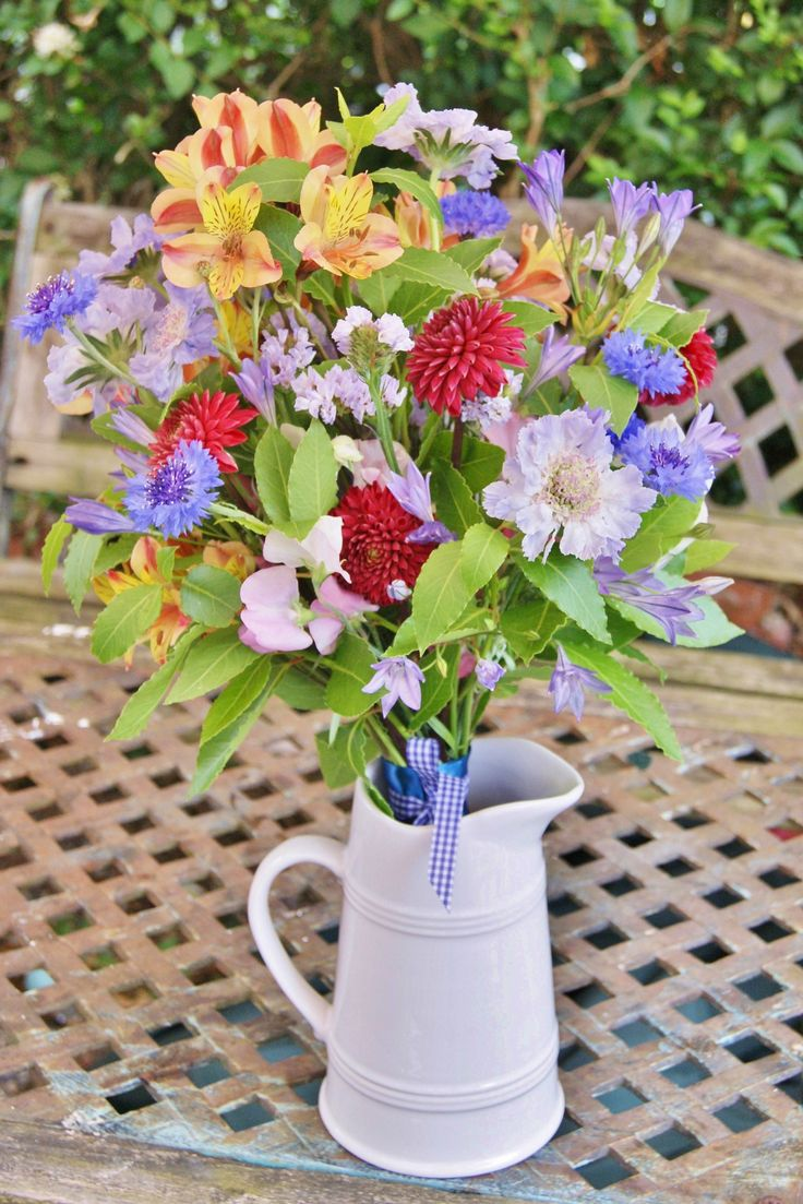 Multi-coloured hand-tied bridal bouquet of British-grown flowers for a festival-themed wedding. Red dahlia, pale purple scabious, orange alstroemeria, blue cornflower, blue brodiaea, pal purple statice and pink sweet peas. Florissimo, Shropshire