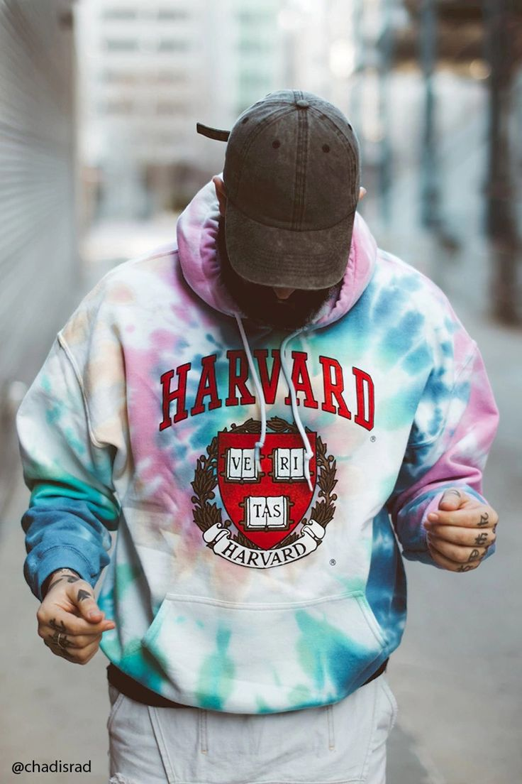 """A fleece knit hoodie in a tie dye wash featuring a """"Harvard"""" graphic with the college's logo on the front, long sleeves, a kangaroo pocket, a drawstring neck, and ribbed trim."""