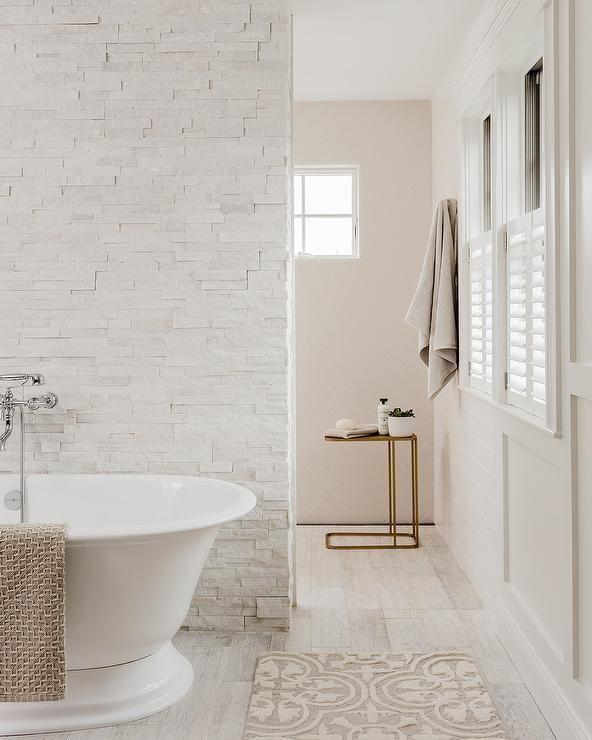 Custom Bathroom Design Featuring A White Staggered Stone Wall Behind A Roll Top Bathtub Paired With A W Custom Bathroom Custom Bathroom Designs Bathroom Design