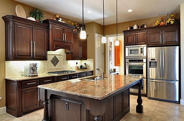 This kitchen by Highland Homes looks super - love the dark mahogany stain with the granite and stainless steel.