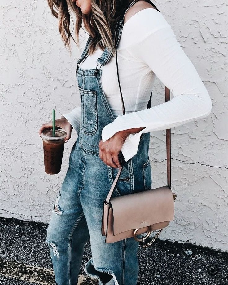 Distressed denim overalls with white top and chic beige handbag.