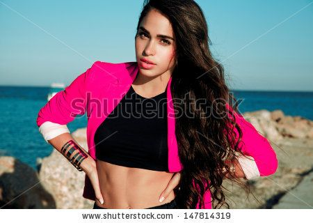 Fashionable brunette woman with long hair in summer outfits and pink Jacket  posing on a sunny day near the sea. outdoors shot.