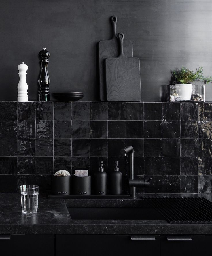 Black tile backsplash in kitchen with black cutting boards