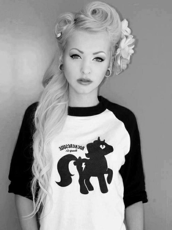 pinned up hairstyles for long hair, platinum blonde young woman with heavy make up and flesh earrings, three fake flowers in hair, black and white pony t shirt