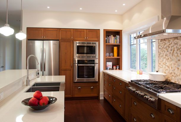 Black Creek Ravine House - The brightly lit kitchen opens onto the large living room, offering views of both the front and back of this forested lot.