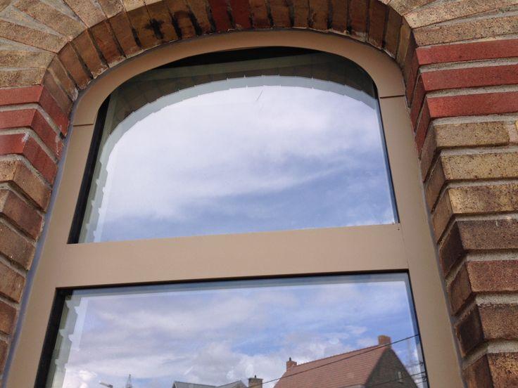 Ramen met een valse center.  Van buiten gezien lijken de ramen gebogen. Van binnen gezien zijn de ramen recht. Er werd een alu boog op de kader gekleefd om zo het uitzicht van gebogen ramen te bekomen.