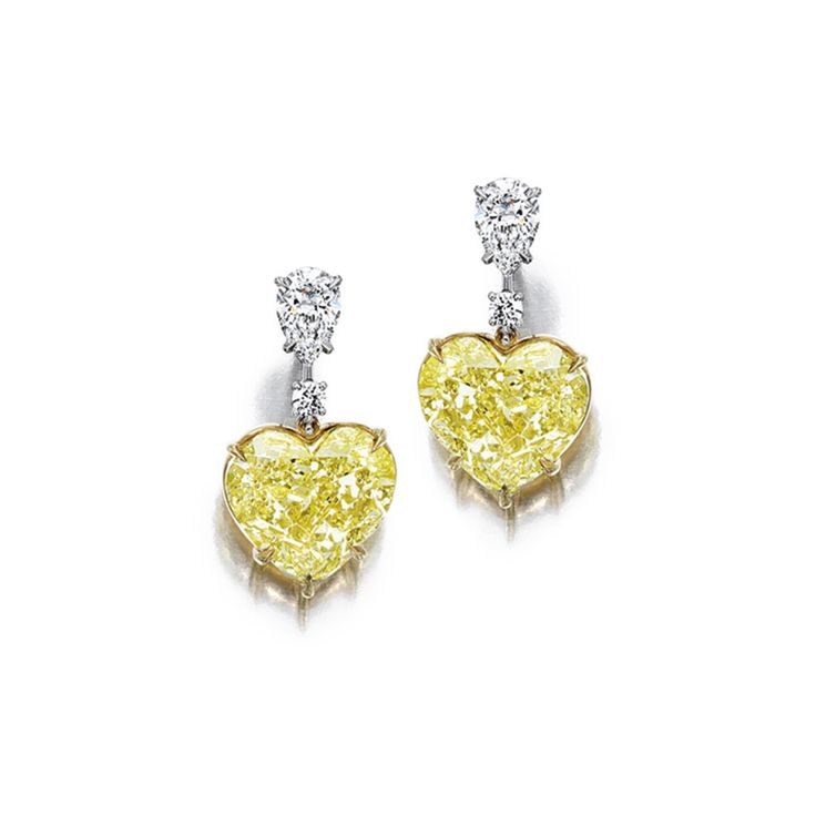 Pair of Fancy Yellow Diamond and Diamond Pendent Earrings Each suspending a heart-shaped fancy yellow diamond weighing 7.43 and 7.08 carats, surmounted by a pear-shaped diamond, mounted in platinum and 18 karat yellow gold.