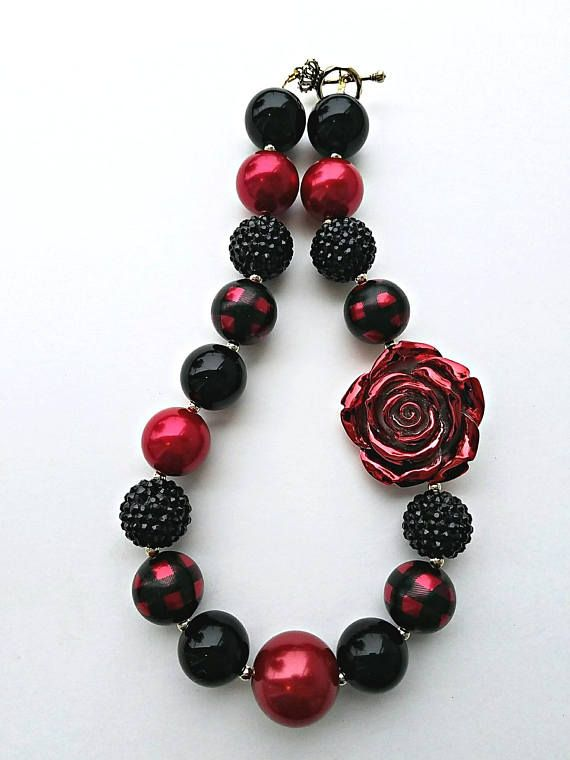 This red and black plaid rose necklace is great for any occassion! Great for birthdays, dress up, photo prop, gifts, stocking stuffers and etc. This necklace has rhinestone beads, plaid beads, rose bead, and more. It has gold spacers and toggle and clasp. Buffalo Plaid