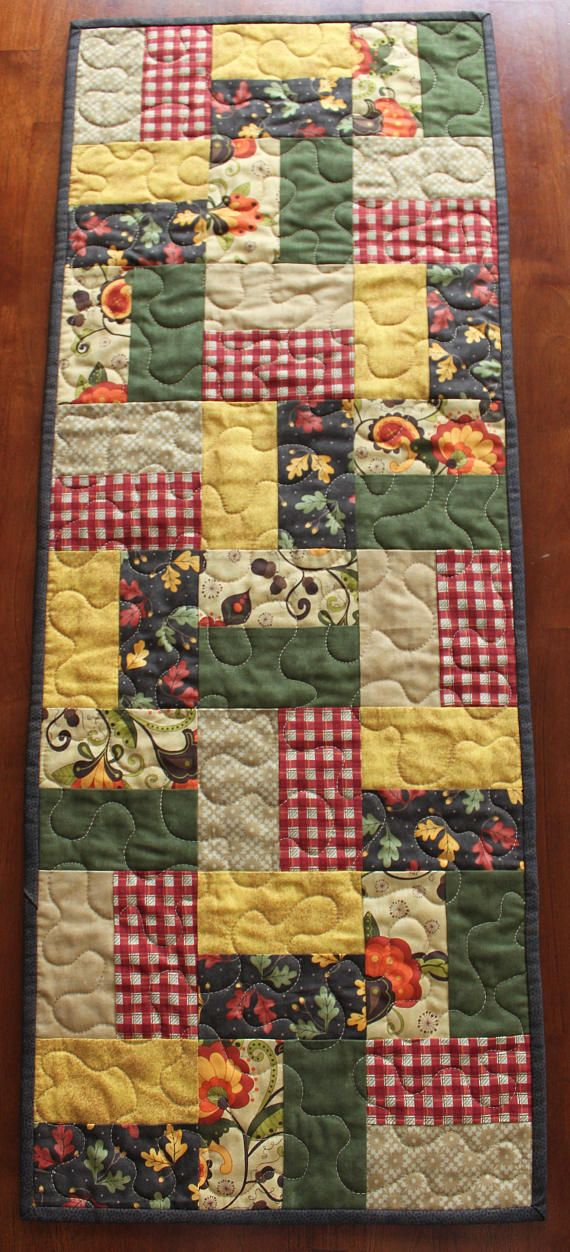 "This beautiful fall quilted table runner was created with various fall fabrics from Sandy Gervais for Moda Fabrics. The fabrics feature leaves, fall flowers, plaids, solids and various patterns in tan, red-orange, green, brown, yellow and orange. The warm colors are perfect to brighten up your table during the fall season and Thanksgiving. This table runner measures approximately 14"" by 36"" and is the perfect size to decorate your dining room table, coffee table, or any other surface that…"