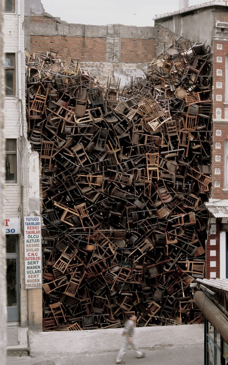 """Doris Salcedo, Installation at 8th International Istanbul Biennial, 2003.  Salcedo's idea was to create a """"topography of war,"""" not tied to a specific historical event, but to war in general. Seeing these 1,550 wooden chairs piled high between two buildings in central Istanbul, one is reminded of mass graves, anonymous victims... of both chaos and absence, two effects of wartime violence."""