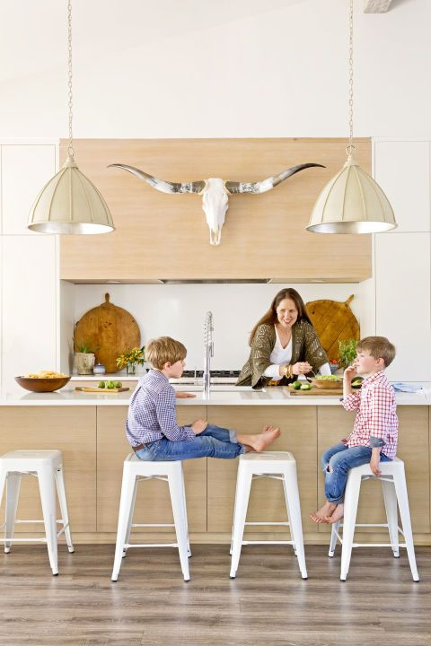 The kitchen cabinets (and the smart appliance-concealing cabinet panels) are made from a custom white-washed oak. The Caesarstone countertops and backsplash, metal stools, and silver-leafed wrought-iron pendant lights make for a handsome trio. And the longhorn? Well, when in Texas...