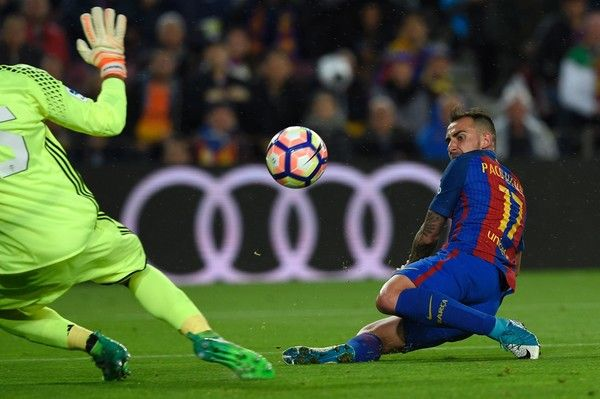 Barcelona's forward Paco Alcacer scores a goalpast Osasuna's Italian goalkeeper Sirigu during the Spanish league football match FC Barcelona vs CA Osasuna at the Camp Nou stadium in Barcelona on April 26, 2017. / AFP PHOTO / LLUIS GENE