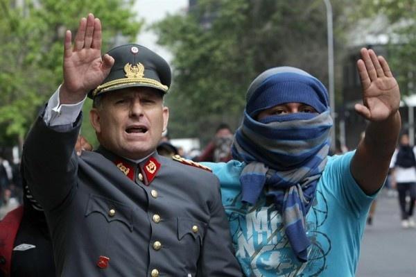 Santiago de Chile - 2011: Un oficial del ejército chileno y un manifestante encapuchado, piden a los exaltados en una protesta, detener sus agresiones contra manifestantes y propiedad pública. Foto:Mario Ruiz de Agencia EFE.