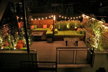 Evening Garden in Wicker Park  by Chicago Specialty Gardens, Inc.	  On a modest garage rooftop in Chicago's Wicker Park CSG installed an eclectic mix of elements including a shade structure of ipe and black bamboo, ipe privacy screens, mixed plantings, colorful cushions and pillows, and a lighting scheme which brings the garden alive after dark.