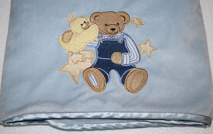 An adorable Blue Jean Teddy Bear Blue Baby Blanket. The teddy bear is Holding a Duck with Stars around bear. BJT Velour topside with Satin Back #BlueJeanTeddy