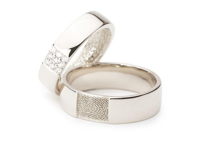 Twee witgouden trouwringen met een vingerafdruk. De damesring heeft de vingerafdruk aan de binnenzijde en is voorzien van negen diamanten. De herenring heeft aan de buitenzijde een verdiept rechthoekig vlak waarin de vingerafdruk is geplaatst.