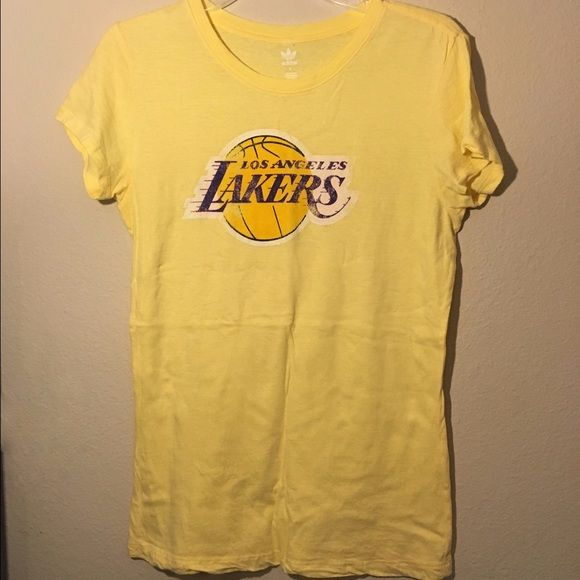 """Women's Lakers t-shirt Yellow Los Angeles Lakers t-shirt. Lettering is NOT faded/smeared. This is how the shirt was made. My ex is a season ticket holder and he bought this for me before we went to a game. I only wore it that night for a few hrs, washed it and it's been hanging in my closet since. 17"""" from Armpit to Armpit. **NOTE: color is more the 1st pic  Ask any questions before purchasing!! 💝  🚭 Smoke Free House 🐶 Pet Free House ✅ Bundle Discount 👎 Low Ball Offers 🚫 No…"""